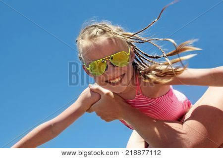 Happy little girl in a Sunny yellow with glasses and pigtails on the head and on the hands of the father on the summer sea.