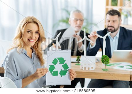 Ecological project. Positive beautiful smiling woman feeling confident while showing a recycling symbol with her smart enthusiastic colleagues sitting behind her and working at the windmill turbines