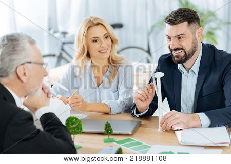 Emotional communication. Positive polite emotional engineer feeling excited while sitting with his colleagues and showing them a tiny model of a progressive windmill turbine