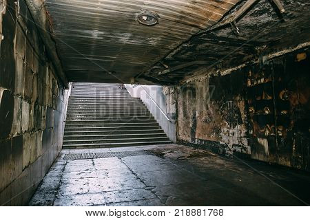 Consequences of fire in underground tunnel or dark corridor or crossing way. Charred walls of corridor and steps