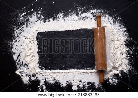 rolling pin and white flour on a black textural background. Free space for text. View from above.