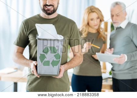 Recycling paper. Happy young man showing a nice bin full of recycled paper with a recycling symbol on it while his colleagues standing near and working