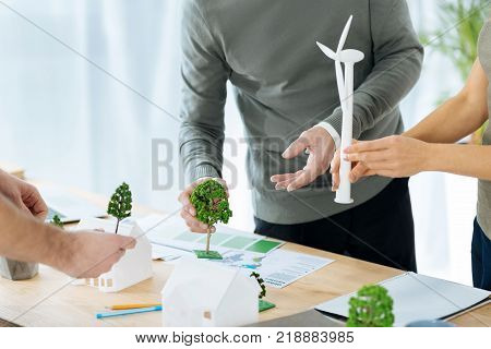 Beautiful miniatures. Creative enthusiastic skilled engineers developing their imagination while taking adorable tiny models of houses and mixing them with the models of windmill turbines and trees