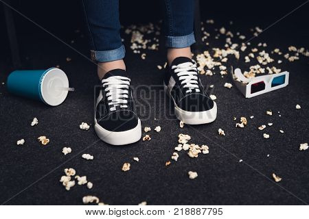 low section of female legs on messy floor in movie theater