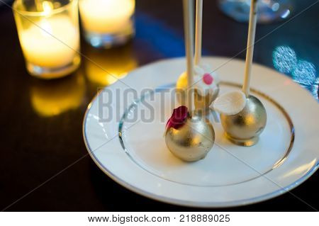 Chocolate cake pops with gold elegant New Year's or Celebration Rich Chocolate dessert photography with chocolate truffle balls draped in chocolate and gold  with white chocolate flowers for coffee or dessert conceptual Christmas and New Year's eve elegan