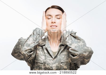 Homeland calling. Appealing calm earnest woman standing in combat uniform and placing  her hands on the head while closing her eyes