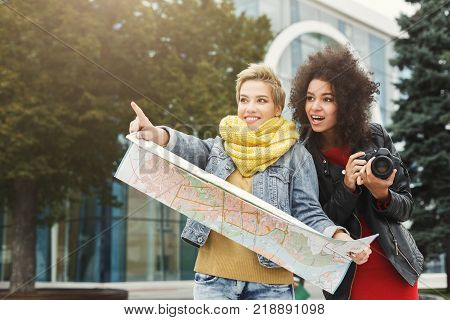 Two girls with paper map outdoors. Female friends walking around late autumn city, taking photos and having fun. Travelling, tourism, leisure, friendship, hobby and digital photography concept