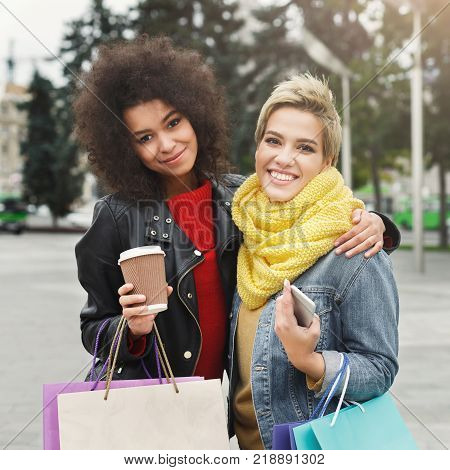 Happy girls with shopping bags and take away outdoors. Smiling female friends in bright warm casual clothes having a city walk. Friendship, urban lifestyle and leisure concept