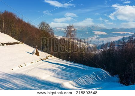 haystack on snowy rural hillside near forest. lovely countryside winter scenery in mountains
