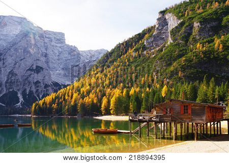 Amazing view of Braies Lake - Lago di Braies - with autumn forest and mountains reflected in surface lake water, Dolomites, Italy, Europe