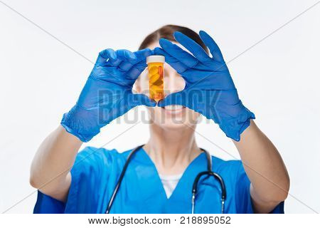 Bottle of medication. Selective focus of female doctors hands wearing blue gloves and holding bootle  which stuffed with medication