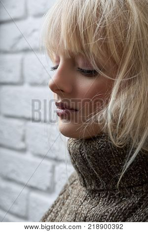 Cropped vertical close up of an attractive young woman posing elegantly near the wall with her eyes closed copyspace beauty makeup natural charming relaxed harmony peaceful.