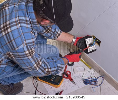 The technician wears the normal protective devices. Electrician's hands assembles a standard bipolar wall socket.
