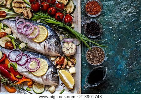 Dorada fish with vegetables lemon spices and greens on a blue background