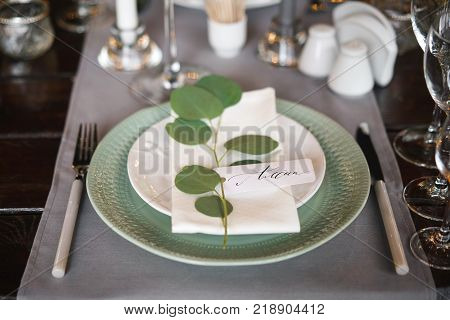 personal seating chart on a dinner party plate. The name written in ink and a pen calligraphy on white designer paper.