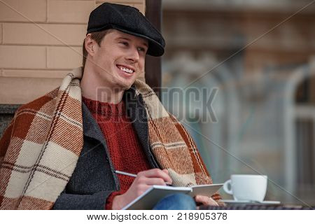 Portrait of handsome author working on book while sitting in chair outdoors. He is enjoying hot beverage while covered with soft cozy blanket