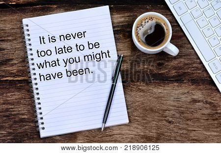 It is never too late to be what you might have been. Inspirational quote on notepad