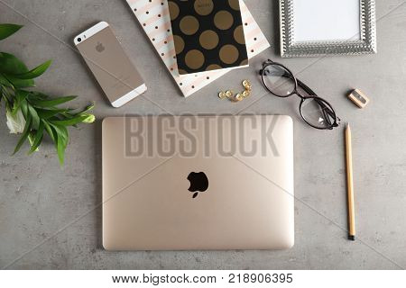 KYIV, UKRAINE - OCTOBER 24, 2017: Apple MacBook Gold and iPhone SE Gold on grey background, top view