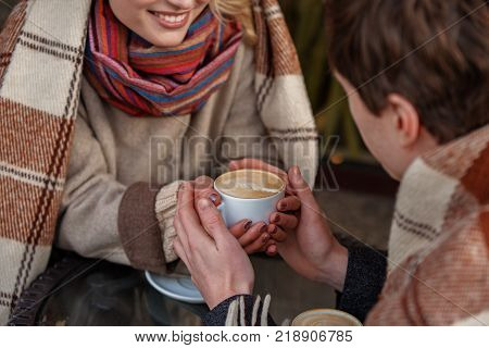 Close up of male and female hands keeping mug of hot drink while covered with soft blankets