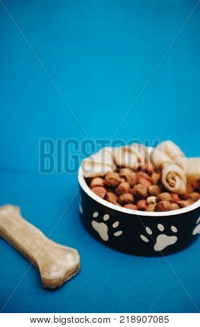 Feed your buddy.A bowl of dry dog food, twisted snacks and a chew bone on a bright one-color blue background. Pet care and veterinary concept. Spase for your text or image.