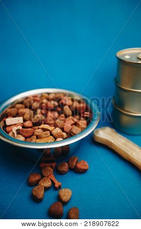 Nutritious meal for your little buddy. A bowl of dry pet food, canned pet meal and a bone treat for dogs on a bright one-color blue background. Pet care and veterinary concept. Spase for your text or image.