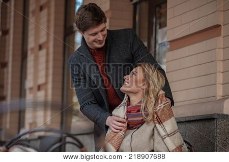Tender moment. Waist up portrait of charming couple enjoying time together outdoors. Lady is looking into eyes of her beloved and smiling