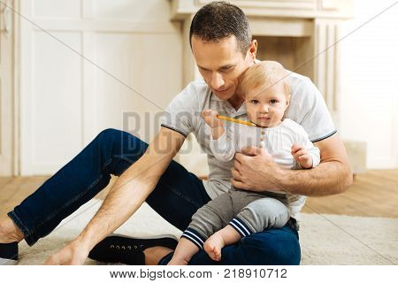 Quiet child. Adorable calm little child spending time with a kind attentive young father while sitting on his leg and holding a pencil
