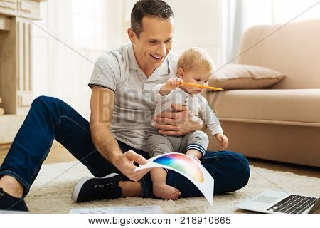 Interesting activity. Positive kind attentive father feeling happy while spending time with his cute little child and sitting in front of a laptop together with a color palette in one hand