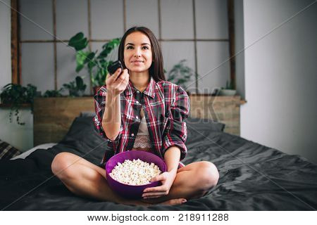 Woman watching funny movie laughing. Beautiful girl watching TV.