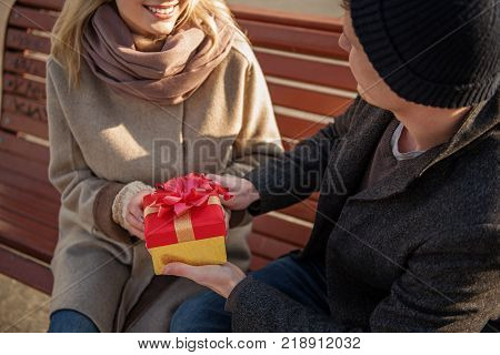 Close up of gift in hands of amorous couple sitting on bench outside. Male is looking at female while lady is smiling