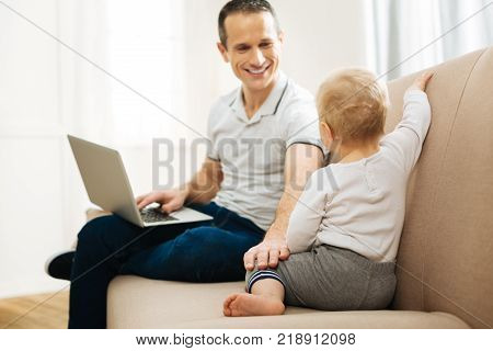 Loving parent. Handsome young attentive father sitting at home with a laptop on his knees and kindly looking at his little cute curious child and smiling