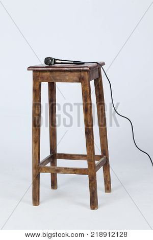 This is a photo of a microphone sitting on top of a wooden stool lite from above. Shot on a white background.