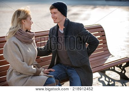 Waist up portrait of lovely amorous couple sitting on bench outdoors. Man is holding gift behind back while woman is looking at him expressing delight