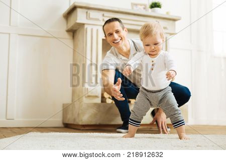Support. Emotional young happy father showing his love and support while a pretty little child trying to stand up and make some steps