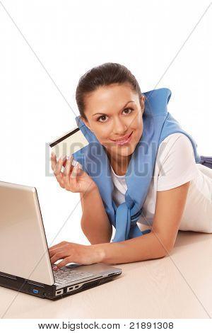 Eine junge Frau mit einem Laptop, auf dem Boden liegend halten eine Kreditkarte