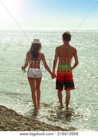 The silhouette of a beautiful young couple standing by the water's edge at sunset, Silhouette of love.