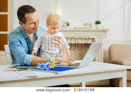 Positive activity. Kind responsible attentive father feeling glad while sitting at the table with his pretty little child and showing him a lovely easy educational game on the screen