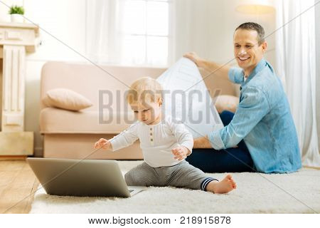 Modern child. Pretty interested curious child sitting on the floor in front of a big modern laptop while his kind attentive cheerful father sitting behind his back and holding a graphic