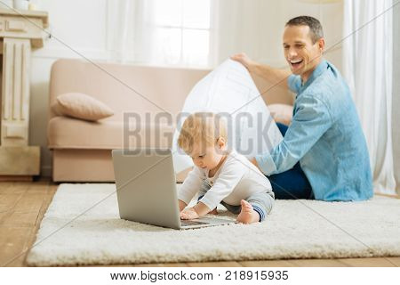 Progressive baby. Funny cute progressive baby feeling busy while trying to type on a modern laptop with his attentive cheerful father sitting behind his back and looking at this adorable process