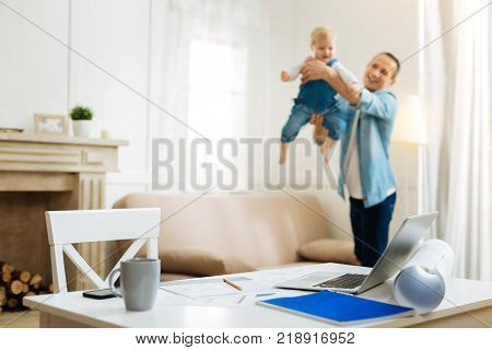 Favorite game. Cheerful kind attentive father having fun with his cute little baby after coming home from work and leaving all the important tasks on the table