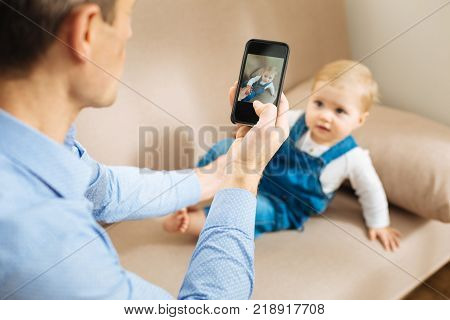 Memorable moment. Calm kind attentive father feeling concentrated while being at home and taking a lovely photo of his cute little child relaxing on a soft sofa