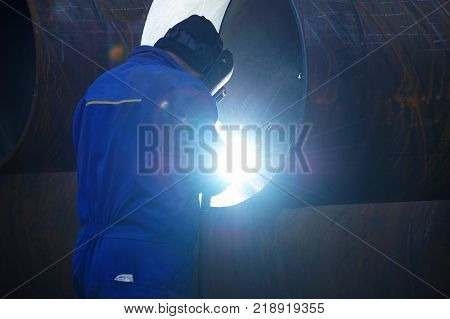 Industrial electrode welder with face shield and blue overall welding a steel pipe in workshop. Back view.