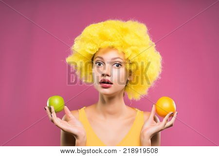 a girl in a clown suit with a serious expression of her face holding apples