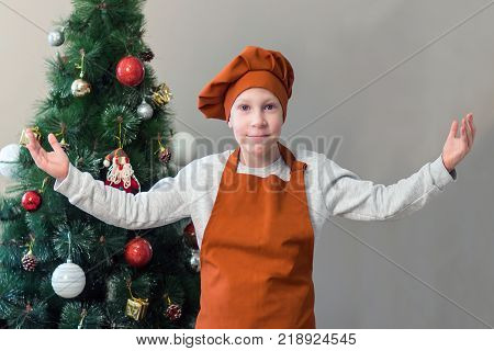 A cute young smile boy in the orange form of a cook raised his hands inviting everyone to the New Year's table or to prepare a festive meal. Decorated Christmas tree on a gray background.