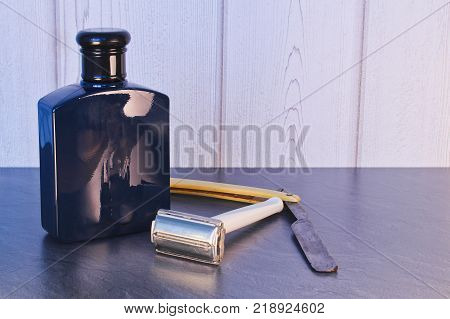 Old retro razor blade with after shave lotion on stone table