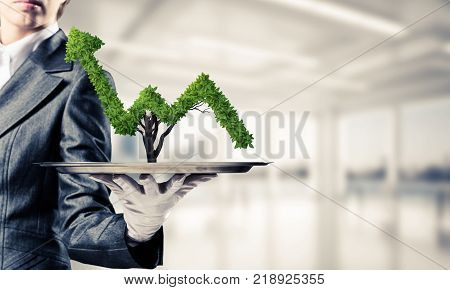 Cropped image of waitress's hand in white glove presenting green growing graph on metal tray with office view on background.