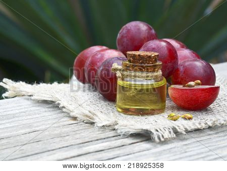 Grape seed oil in a glass jar and fresh grapes on old wooden table in the garden.Bottle of organic grape seed oil for spa and bodycare and grape berries.Spa,Bio,Eco products concept.Selective focus.