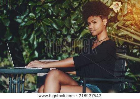 Side view of charming young black woman sitting outdoors in the garden with laptop and looking at the camera; portrait of beautiful curly Brazilian female in street cafe in city park with netbook