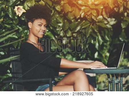 Smiling young African American female student sitting at the table in park and looking at camera while using her laptop; black cheerful girl with curly Afro hair working on her netbook in a garden
