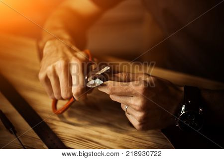 Working process of the leather belt in the leather workshop. Man holding crafting tool and working. Tanner in old tannery. Wooden table background. Close up man arm. Warm Light for text and design.